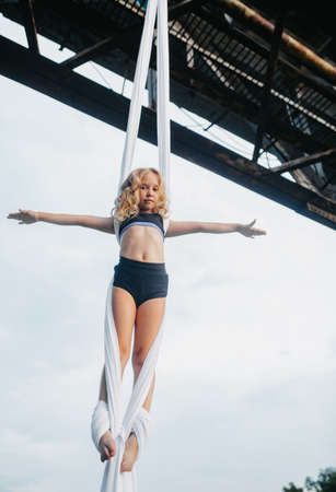 Child girl aerialist performs acrobatic tricks on hanging aerial silk attached to the bridge support against background of sky.