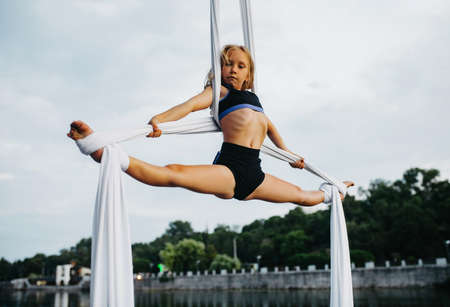 Child girl aerialist performs gymnastic split on hanging aerial silk against background of river, sky and trees.