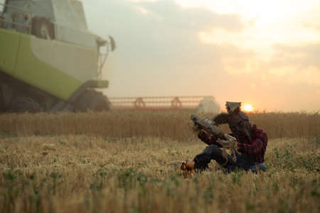 Man in image of sorcerer in hat with rabbit ears sits near doll among wheat field and performs a magic ritual holding old toy car in his hands against sunset sky and harvester. Stock fotó