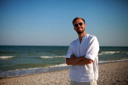 Young smiling man in sunglasses stands on beach against sea and sky background. Copy space.