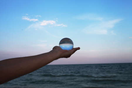 Human hand holds crystal ball. View through it to sea, sky and horizon line. Effect of optical illusion.