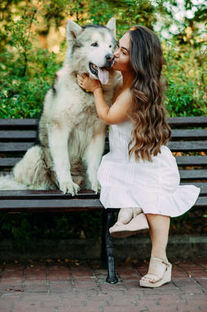 Young woman with innate disorder dwarfism sits on bench next to Malamute dog, hugs and kisses it while walking in park.