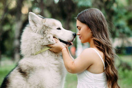 Young woman with innate disorder dwarfism embraces Malamute dog while walking in park. Portrait.