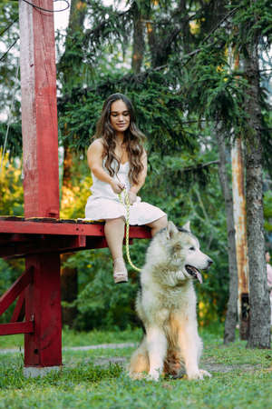 Young woman with innate disorder dwarfism sits on bench next to Malamute dog and keep on a leash it while walking in park.