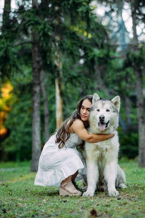 Young woman with innate disorder dwarfism embraces Malamute dog while walking in park.