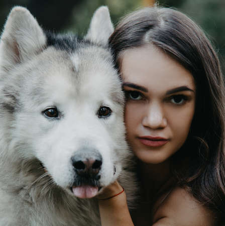 Portrait of young brunette woman with Malamute dog in park. Zdjęcie Seryjne