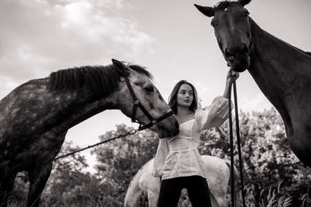 Young woman stands in pasture near two horses and holds them by bridle. Black and white image.