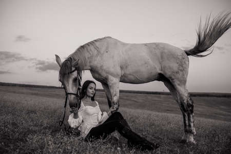 Young pensive woman sits near gray horse in pasture. Black ans white image.