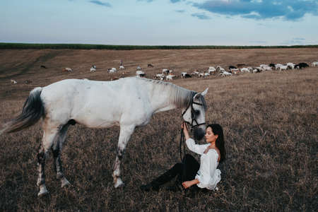 Young woman sits near gray horse in pasture against background of grazing goats in the distance.
