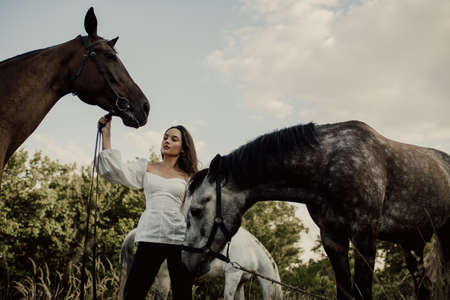 Young woman stands in pasture near two horses and holds them by bridle.
