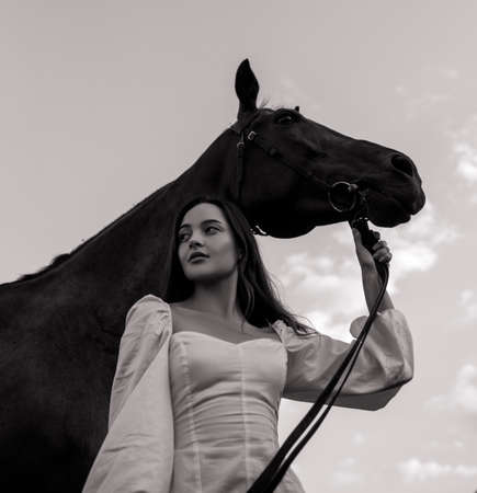 Young woman stands and holds horse by bridle against sky background. Black and white image.