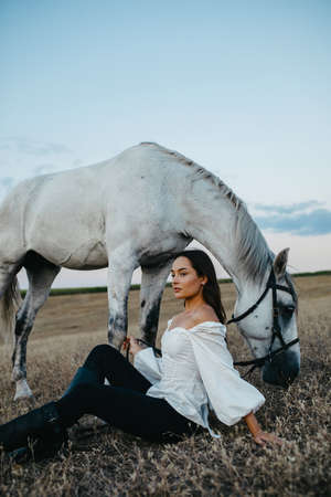 Young pensive woman sits near gray horse in pasture.