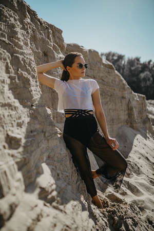 Pretty woman poses in sand canyon against background of rocks and blue sky.