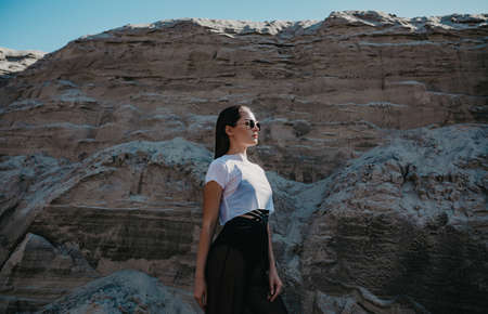 Pretty woman with sunglasses poses in canyon against background of rocks. Zdjęcie Seryjne