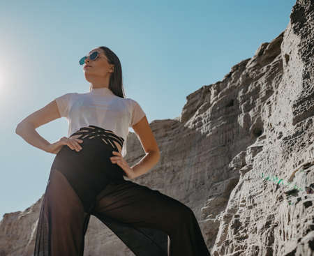 Pretty woman in sunglasses poses in canyon against background of rocks and blue sky.