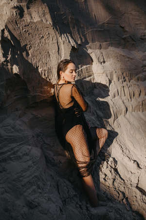 Pretty woman in black transparent dress poses in sand canyon.