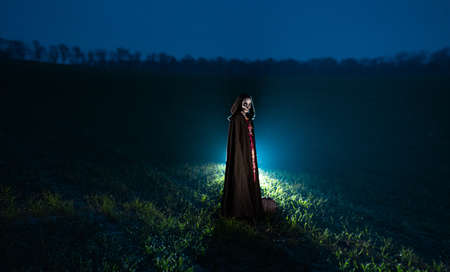 Young woman stands among field in Halloween costume of death with painted skeleton on her body against dark sky. Halloween concept. Sugar skull makeup. Backlit.
