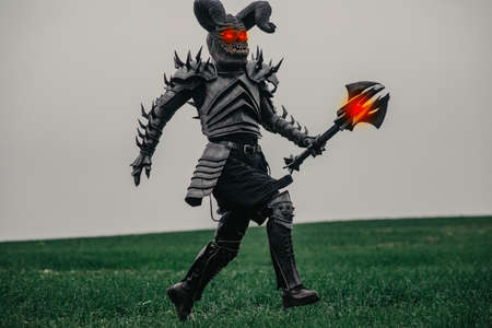 Mutant warrior runs on meadow with glowing eyes and holds mace in his hands.