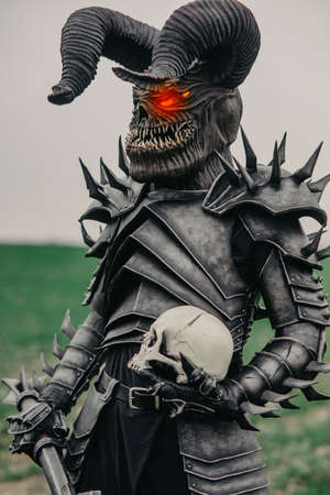 Mutant warrior stands with glowing eyes and holds mace and a human skull in his hands.