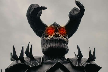 Portrait of a mutant warrior in armor with terrible teeth, horns and glowing eyes against sky background.