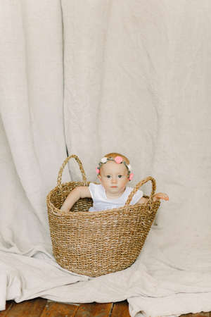 Baby girl with wreath on her head sits and peeks out from wicker basket.