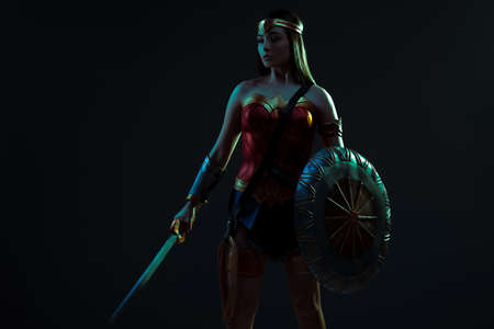 Girl in image of ancient woman warrior stands with sword and shield in her hands against of dark background.