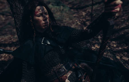 Woman in chain mail in image of medieval warrior sits and rests near tree among forest. Closeup.