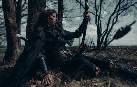 Woman in chain mail in image of medieval warrior sits and rests near tree among forest. Stock fotó