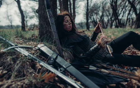 Woman in chain mail in image of medieval warrior lies and rests near tree among forest.
