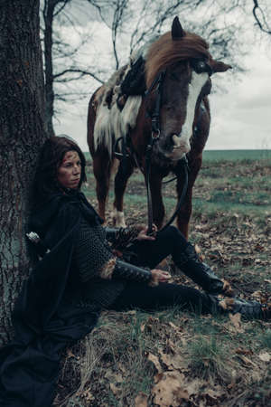 Woman in chain mail in image of medieval warrior sits and rests near tree among forest and holds horse by the reins.