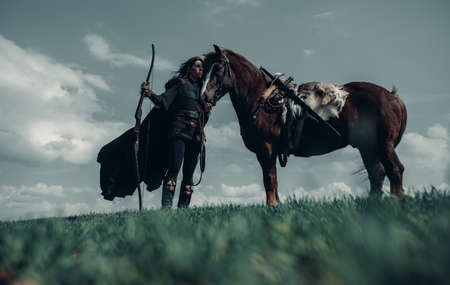 Woman in chain mail in image of medieval warrior stands with bow in her hand near horse in field.