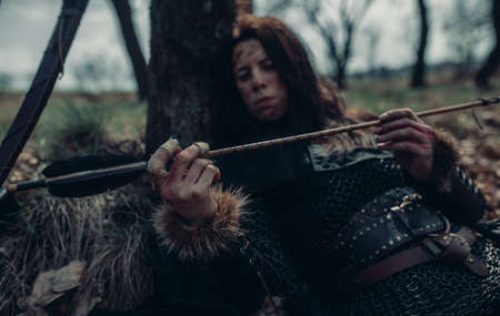 Woman in chain mail in image of medieval warrior lies, rests and examines her arrow near tree among forest. Focus on her hand. Stock fotó