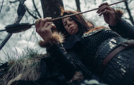 Woman in chain mail in image of medieval warrior lies, rests and examines her arrow near tree among forest.