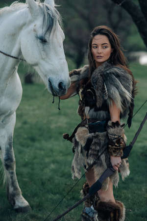 Woman stands in fur clothes in image of ancient warrior amazon with bow in her hands in forest near her horse.