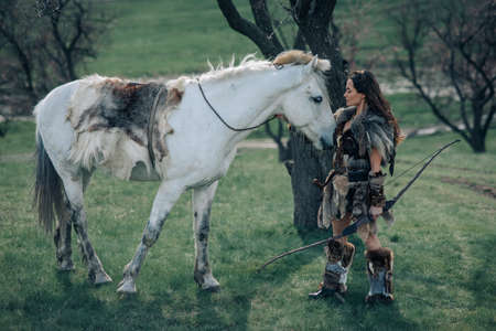 Woman stands in fur clothes in image of ancient warrior amazon with bow in her hands in forest near her horse. Stock fotó