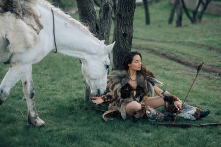 Woman in image of ancient warrior amazon sits and rests with bow and arrow in her hands under tree in forest near her horse.