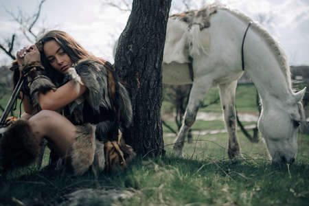 Woman sits and rests on grass in forest in image of ancient warrior amazon with sword in her hands on background of grazing horse.