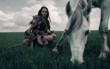 Woman sits on meadow in image of ancient warrior amazon armed by sword near grazing horse. Stock fotó