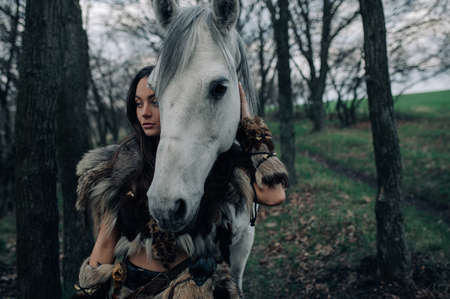 Portrait of woman in image of ancient warrior amazon with her horse in forest.