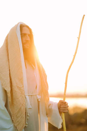 Jesus Christ with wooden staff stands in meadow clothed in his traditional white robe against river and sunset background. Stock Photo