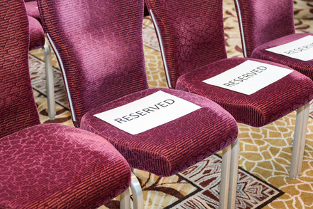 reserved seat: Red rows of chairs with white sheets reserved Stock Photo