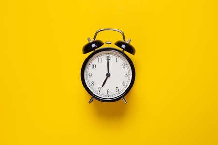 alarm clock shows 7 o'clock on a yellow background