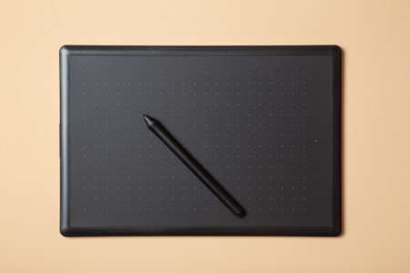 Graphics tablet and stylus on a cream background