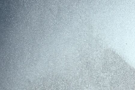 Blue window glass covered hoarfrost ice pattern texture. Cold nature winter background.