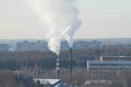 Cloud of smoke rising up from indastrial chimney on background of cloudy sky. Indastrial zone in city of Russia. Winter cityscape with buildings and park. Stock photo with empty space for text.