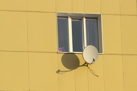Satellite dish fixed to the wall of a tiled house in sunny day. Stock photo for web and print with empty space for text.
