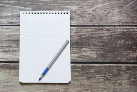 Notepad with a blank white sheet in a checker paper with ball pen lies on the background of wooden boards.