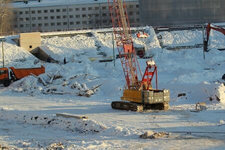 Large crawler crane works at a construction site on a frosty sunny day in winter in Russia.