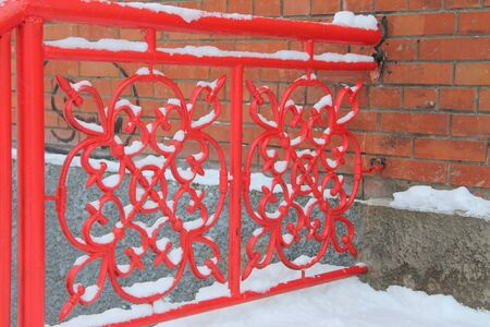 bright red metal gates with floral symmetrical onamement covered with snow. Decorative construction attached to a brick wall. Stock photo for web and print with empty space for text.
