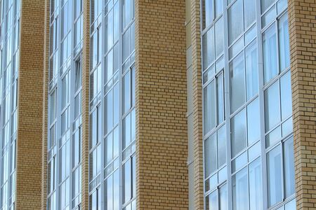 Plastic windows in a modern tiled brick high-rise house. Bottom view. Stock photo modern urban development for web and print. Stock Photo